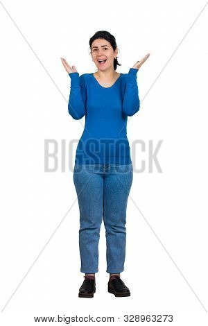 Excited emotive girl smiles broadly, spreads hands or applause, full length portrait against white, expresses positive emotions. Surprised overjoyed young woman exclaims happiness. stock photo