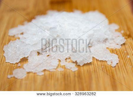 Natural sea salt on wooden background. Anthos sea salt. Flakes of natural sea salt. Crystals of sea salt. stock photo