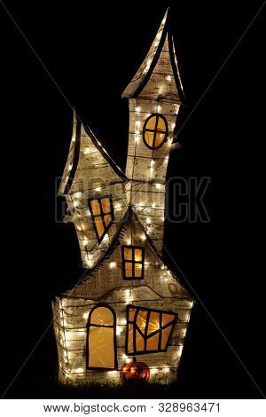 Haunted House Décor for Halloween Lights Up. Isolated haunted castle creating Halloween ambiance outside residential building. stock photo