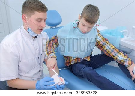 Dentist teaching patient child boy how to clean teeth using toy jaw model. Showing massaging movements with brush for brushing teeth in dentistry. Oral hygiene and everyday care procedure. stock photo