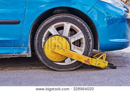 Clamped front wheel of illegally parked car, yellow clamp attached to wheel stock photo