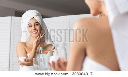 Smiling Millennial Girl Applying Face Cream Moisturizing Skin Standing In Bathroom. Panorama, Selective Focus stock photo