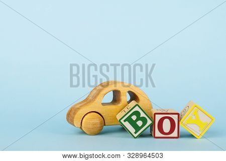 Blue background with colored cubes with letters Boy and wooden toy car, giving birth to a baby boy, toys for toddlers stock photo