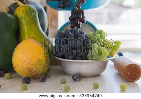 Autumn still life with pumpkins, melons, watermelon, grapes on a scale and in a metal bowl on a wooden white table. Autumn harvest concept. Happy Thanksgiving. Selective focus. Template for design. stock photo