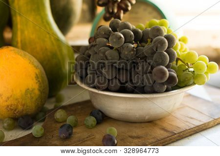 Autumn still life with pumpkins and grapes in a metal bowl, grapes are scattered around on a wooden white table. Autumn harvest concept. Happy Thanksgiving. Selective focus. Template for design. stock photo