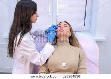 Doctor cosmetologist making injection with filler in mature woman patient cheek on face to moisturize and rejuvenate skin. Beauty procedure against wrinkle in clinic. Preparation with hyaluronic acid. stock photo