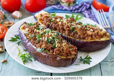 Healthy dinner. Snack. Stuffed with minced meat and vegetables eggplant on wooden table. Free space for your text. stock photo