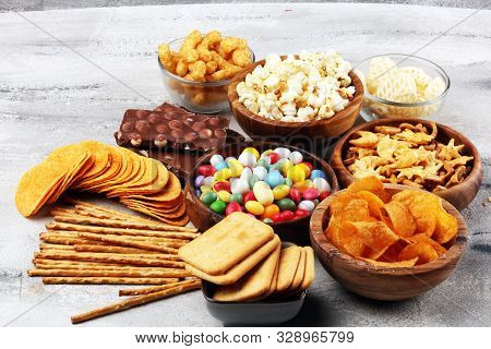 Salty snacks. Pretzels, chips, crackers in wooden bowls. Unhealthy products. food bad for figure, skin, heart and teeth. Assortment of fast carbohydrates food. stock photo