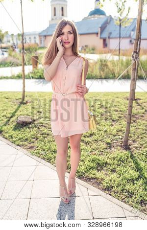 beautiful girl in pink dress, makes phone calls, summer in city park, holds smartphone, listens to audio message on Internet, online application in social networks talking. stock photo