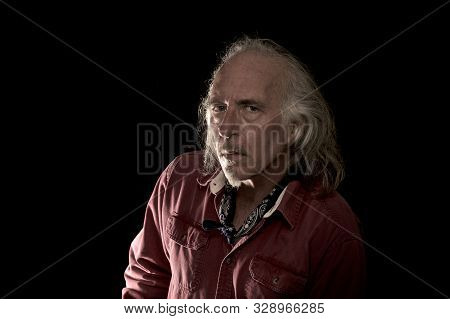 An old grizzled looking cowboy with red shirt and blue bandana, long hair and mustache and goatee looking intently at camera. stock photo
