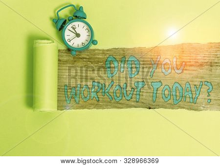 Handwriting text writing Did You Workout Today. Concept meaning asking if made session physical exercise Alarm clock and torn cardboard placed above a wooden classic table backdrop. stock photo