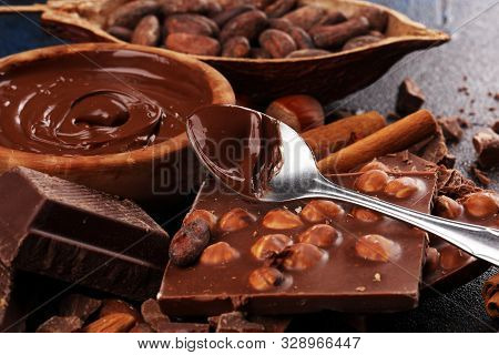 Chocolate bar pieces and melting swirl cocoa. Sweet food photo concept. The chunks of broken chocolate on rustic background with nuts and spices stock photo