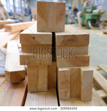 View from butt of stack of three-layer wooden glued laminated timber beams from pine finger joint spliced boards for wooden windows stock photo