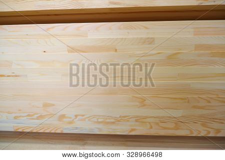 Side view of stack of two-layer wooden glued laminated timber beams from pine finger joint spliced boards for wooden windows stock photo
