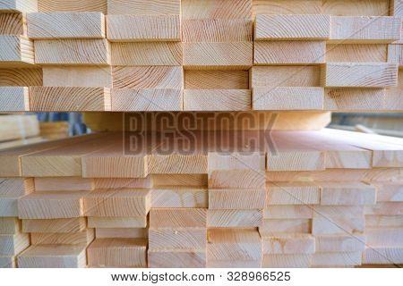 End view of stack of three-layer wooden glued laminated timber beams from pine finger joint spliced boards for wooden windows. stock photo