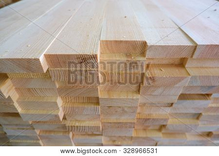 Top-end view of stack of three-layer wooden glued laminated timber beams from pine finger joint spliced boards for wooden windows stock photo