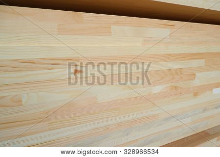 Side view of stack of three-layer wooden glued laminated timber beams from pine finger joint spliced boards for wooden windows stock photo