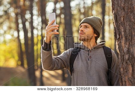 Stay connected. Young guy checking for mobile internet in the middle of autumn forest, hiking alone, copy space stock photo