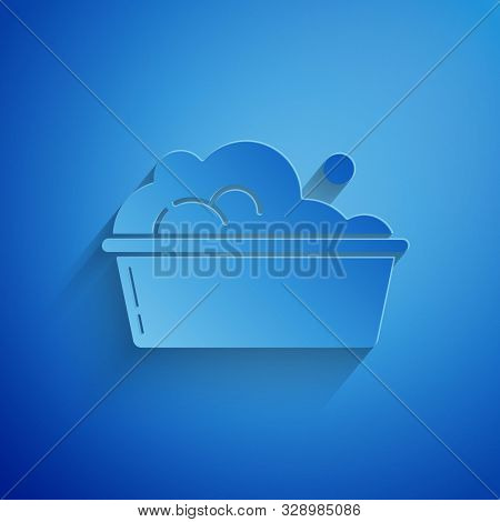 Paper cut Plastic basin with soap suds icon isolated on blue background. Bowl with water. Washing clothes, cleaning equipment. Paper art style. Vector Illustration stock photo