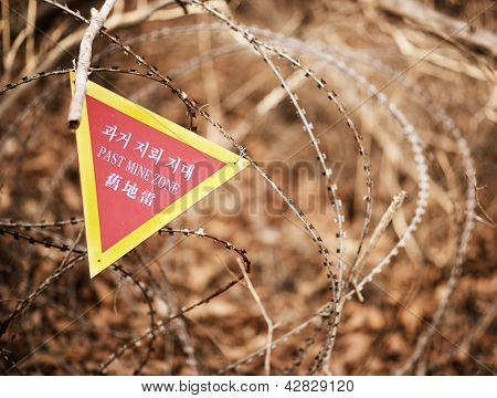A sign indicating the end of a landmine zone in South Korea, a poignant reminder of the unresolved conflict in the region. stock photo
