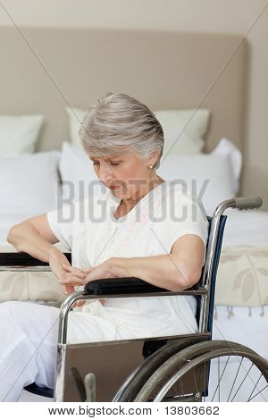 Concentrated senior woman in her wheelchair at home stock photo