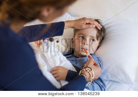 Sick boy with thermometer laying in bed and mother hand taking temperature. Mother checking temperat