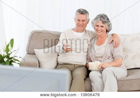 Mature couple watching tv in their living room at home stock photo