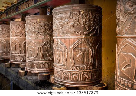 Kora Prayer wheels installed in Tibetan temple. stock photo
