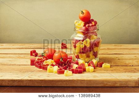 Colorful heart shape pasto with tomatoes on wooden table stock photo