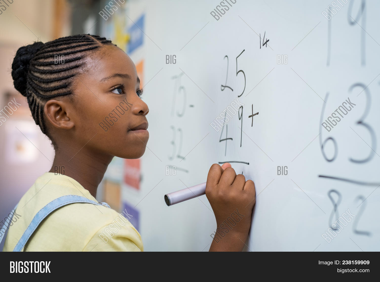 Portrait of african girl writing solution of sums on white board at school. Black schoolgirl solving