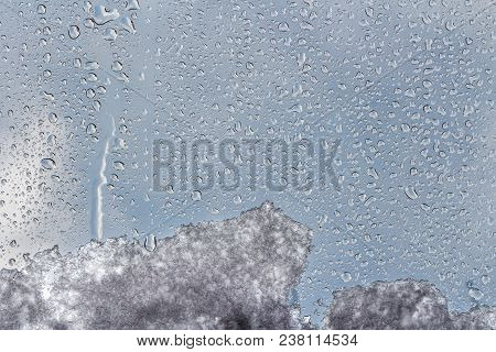 A beautiful horizontal texture of water droplets different size and shape and melting snow and ice is on the glass and on a background of blue sky with white clouds. stock photo