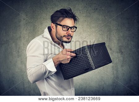 Unsociable man holding a box and looking unwilling to share while posing on gray. stock photo