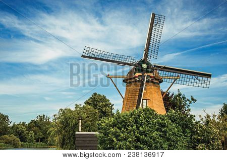 Wooden windmill, leafy bushes and sunny blue sky at Weesp. Quiet and pleasant village full of canals and green near Amsterdam. Northern Netherlands. stock photo