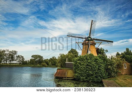 Wooden windmill next to wide river, leafy bushes and green lawn under sunny blue sky at Weesp. Quiet and pleasant village full of canals and green near Amsterdam. Northern Netherlands. stock photo