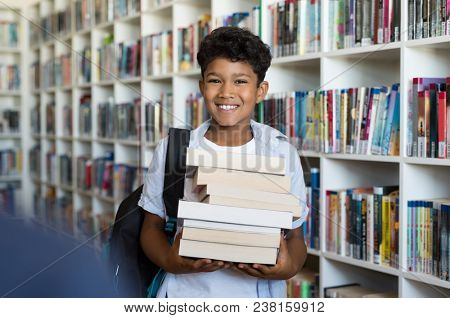Middle eastern boy holding a stack of books against multi colored bookshelf in library. Portrait of happy arab schoolboy with backpack at school. Happy young indian child holding heap of books. stock photo