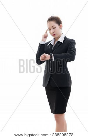 Smiling young Asian businesswoman in black suit and white shirt pointing finger and looking at her watch isolated on white background stock photo
