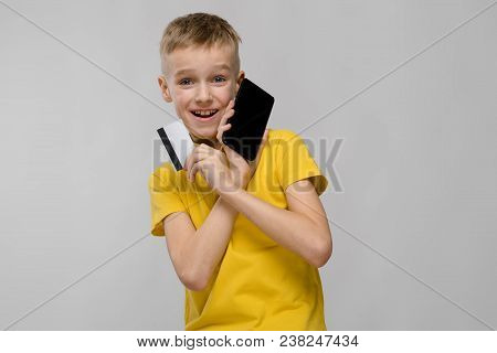 Portrait of smiling teenage boy in yellow T-shirt holding mobile phone and blank credit or business card isolated on grey background with copyspace digital advertising concept. stock photo