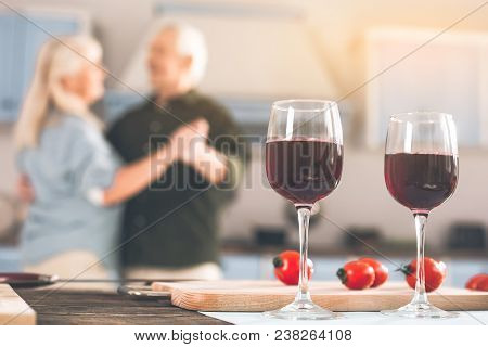 Focus On Two Glasses Of Red Wine On Table. Happy Old Loving Couple Dancing In Kitchen On Background
