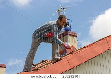 services on painting a roof at the house in a red color stock photo