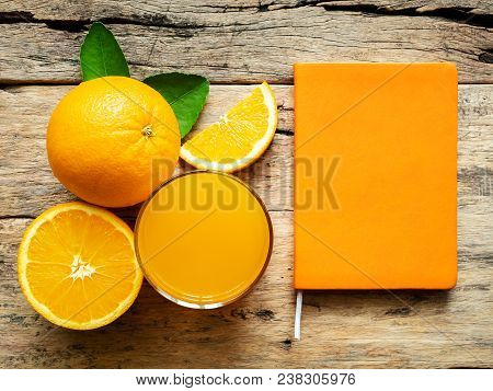 a glass of fresh orange juice and group of fresh orange fruits with green leaves, on wooden background with orange cover book color. vitamin C and fruit product display or montage, studio shot stock photo