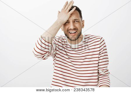 Crap I forgot about meeting. Portrait of embarrassed handsome troubled guy in striped pullover, punching forehead and grimacing, remembering something important and regretting, standing over gray wall. stock photo