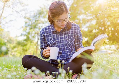 The Girl Sitting On A Green Grass With Cup Of Coffee And Reads The Book. Read Book Woman Summer Outs