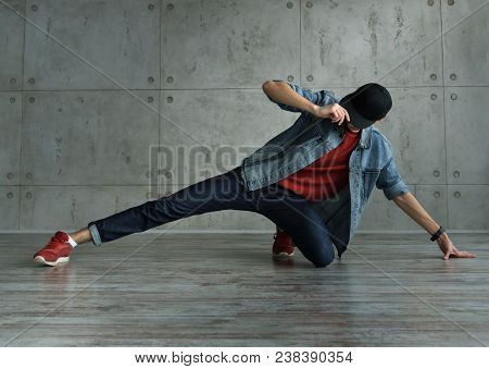 Teenager guy in denim jacket and baseball cap, jeans and red sweater dances of break dance. Dynamics of modern dance movement. Youth fashion. Man is unrecognizable stock photo