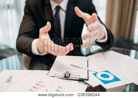 explanation. hand gestures. business man holding in hands. business papers on the desk. office working space stock photo