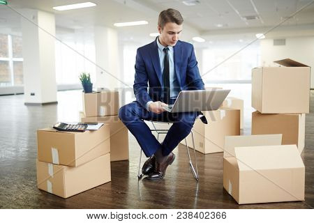 Young employee in elegant suit sitting on chair among unpacked boxes in new office and browsing in the net stock photo