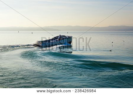 Powerboat sails in Garda lake, Italy. Lake view with boat in Sirmione. Lonely boat in Lake Garda, sunset time. Beautiful landscape with blue water and hills on background. stock photo