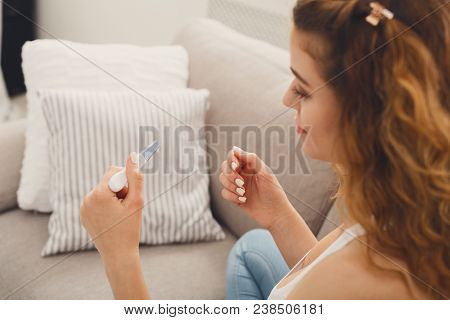 Smiling redhead girl checking her recent pregnancy test, sitting on beige couch at home, copy space stock photo
