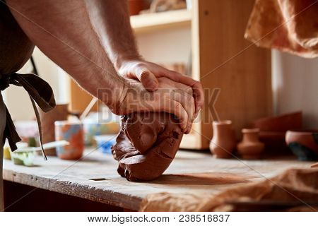 Adult male potter master in dirty apron modeling the clay plate on the potter's wheel. Top view, closeup,selective focus, shallow depth of field, hands only. Art and business, hobby and freelance working concept. Art and crafts concept. stock photo