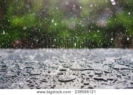 rain drop falling onto blackboard with green nature background stock photo