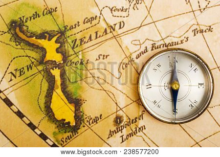 Antique compass and old map of Captain Cook's journeys, showing New Zealand. Map is from 1795 and is out of copyright. Concepts of exploration,navigation,discovery,adventure,history. stock photo